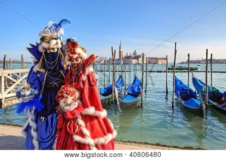 VENICE - MARCH 04: Two participants in red and blue costumes near gondolas on Grand Canal and San Giorgio Maggiore church on background during traditional carnival in Venice, Italy on March 04, 2011.