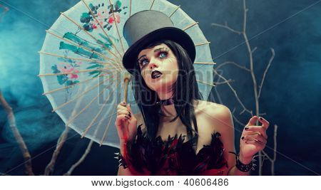 Attractive gothic girl in top hat with Chinese umbrella looking up, studio shot with fog and branches