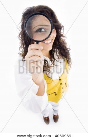 Young Girl Holding Magnifier And Showing Her Magnified Eye