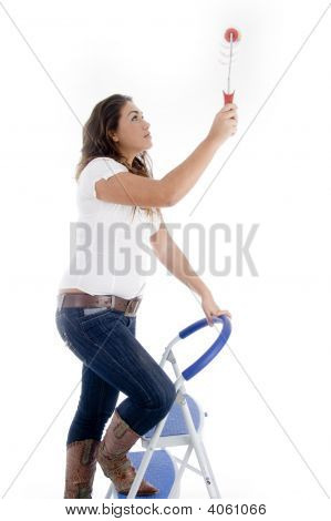 Woman Standing On Ladder Chair And Holding Paint Roller