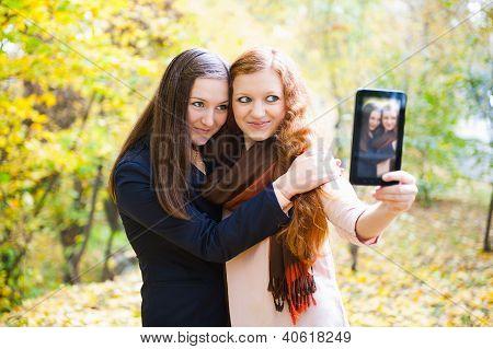 Duas meninas tomando o auto-retrato no Parque Outono
