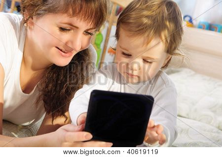 Mother And Baby Son Playing With Digital Tablet