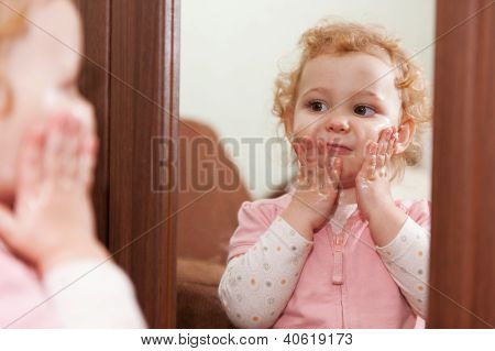 Cute Baby Applying Cream On Her Cheeks