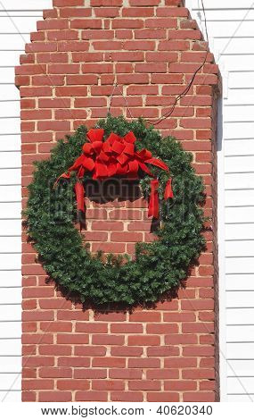 Christmas Wreath With Red Ribbon On Brick Chimney