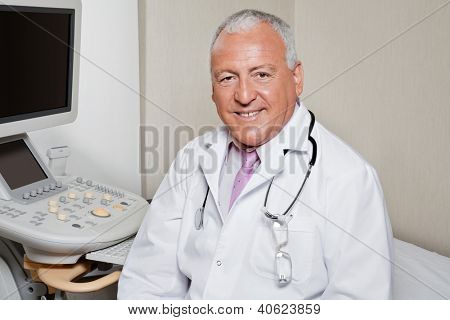 Retrato do radiologista masculino sênior, sorrindo com máquina ultra-sônica no fundo