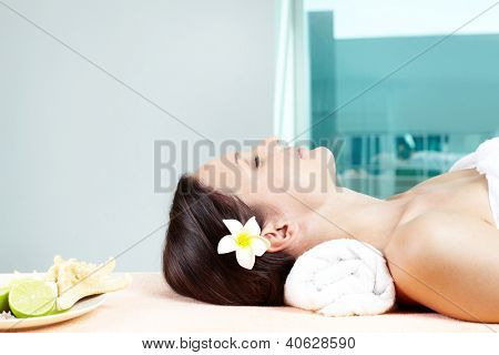 Close-up of a lovely woman lying in spa salon with her eyes closed
