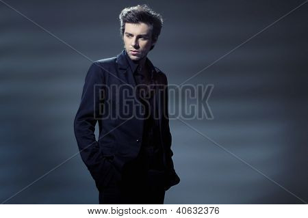 Portrait of a handsome young business man leaning against the wall