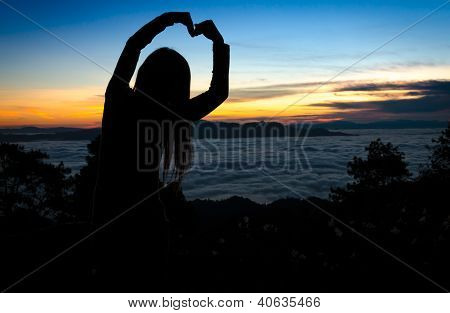 Silhouette Of Woman Making Heart Shape With Arms Over Sunset