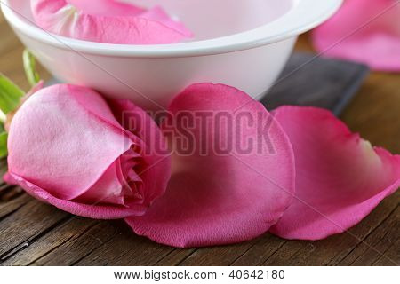 Spa concept with rose petals on a wooden background