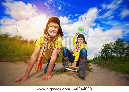 crazy boy and girl are sledding at summer