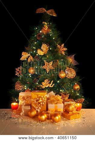 Image of gifts under beautiful Christmas tree isolated on black background, green fir tree decorated with golden balls, stars, angels and garland, different wrapped New Year presents, xmas surprise