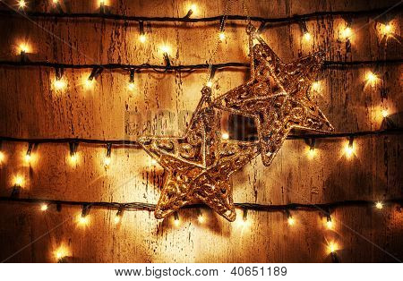 Picture of luxury star decorations hanging on the door adorned with Christmas lights, Christmastime beautiful ornament, golden festive home decor, New Year greeting card, xmas shining garland