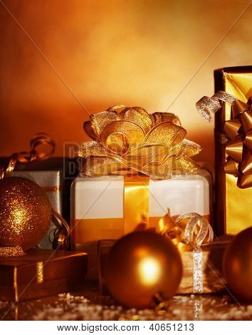 Picture of Christmas gifts variety on dark grunge background, golden wrapping paper, New Year presents, xmas decoration, holiday party, festive ornament, decorative bauble, Christmastime still life