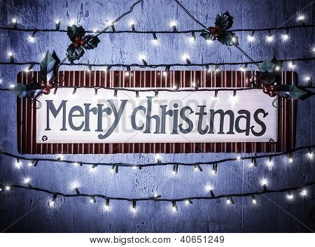 Photo of Merry Christmas banner on blue grunge door at home, happy New Year, glowing electrical garland, Christmastime house interior, congratulations postcard, holiday illumination