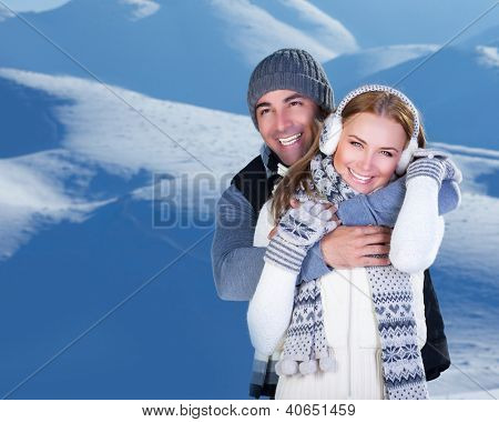 Photo of happy family enjoying winter vacation in snowy mountains, closeup portrait of cheerful smiling couple hugging outdoor in cold weather, romantic date, affection and happiness concept