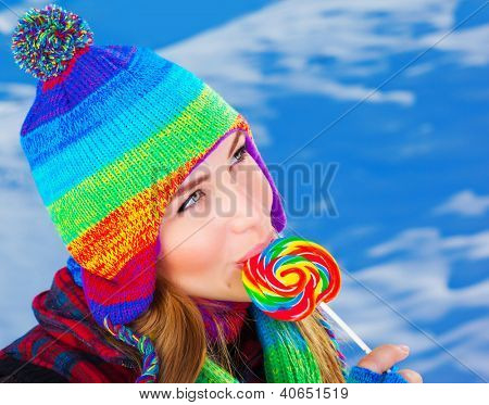 Image of attractive woman licking lollipop outdoors in wintertime, sweet colorful candy cane, snowy background, warm knitted hat, having fun, winter holidays, happiness concept