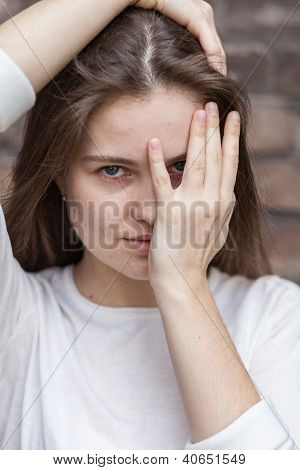 Young Woman Looking Through Fingers