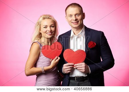 Portrait of elegant happy couple holding paper hearts and looking at camera