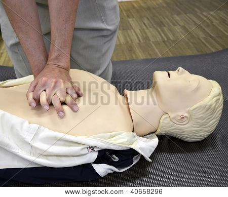 A man practicing CPR techniques on dummy.