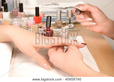 Woman's Hands With Nail Brush Drawing On Nails