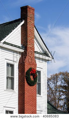 Chimney With Christmas Wreath On White House