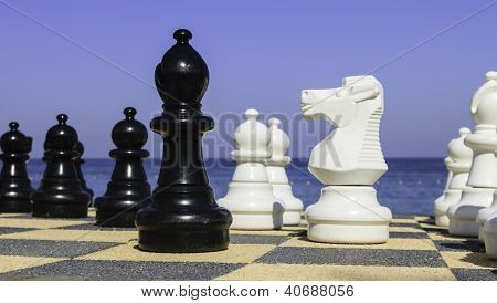 Large Chess Pices Alongside The Ocean