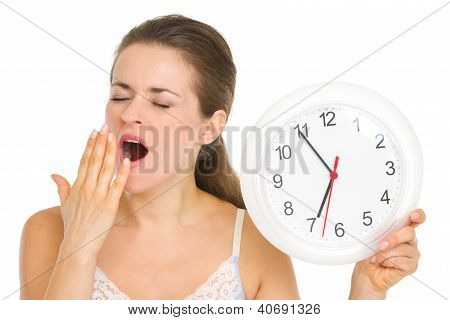 Young Woman With Clock Yawing After Sleep