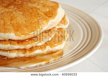 Fresh homemade pancakes with syrup.  Macro with shallow dof.