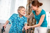 stock photo of crutch  - Senior woman with her caregiver at home - JPG