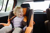 Happy Child Smiling In Car Seat
