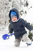 stock photo of snow shovel  - Little boy with shovel playing in snow forest - JPG