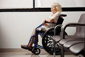 Pensive elderly woman on wheelchair waiting in hospital lobby