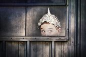 stock photo of peek  - Boy in a tin foil hat peeking out of a window - JPG