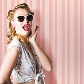 stock photo of pinup girl  - Surprised Young Woman With Pinup Hair Style And Makeup Posing In Striped Copy Space Retro Studio - JPG