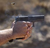 stock photo of lockups  - Handgun that is already back in lockup with brass in the air  - JPG