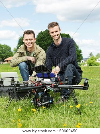 Portrait of male engineers with laptop and digital tablet by UAV at park