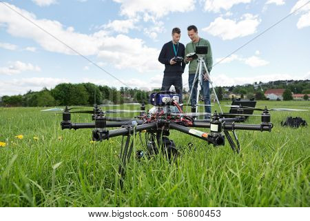 UAV octocopter on grass with engineers discussing in background at park