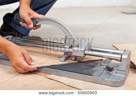 Worker Cutting Floor Tiles With Manual Cutter