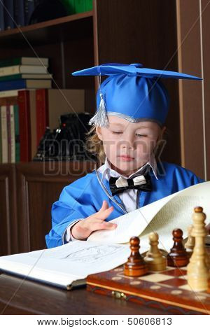 A befuddled little boy leafs through a book