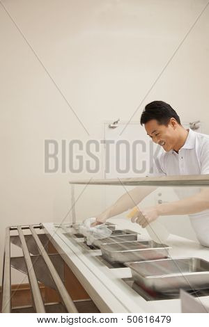 Cafeteria worker cleaning food serving area