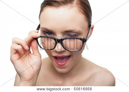 Cheerful model winking at camera over her classy glasses on white background