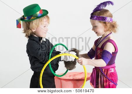 Little boy and girl in costumes of magicians shows trick with a kitten and rings