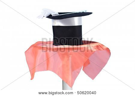 Magician hat, gloves and stick on a table covered with a red cloth