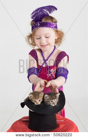Little girl in costume magician pulls out two kittens out of the cylinder