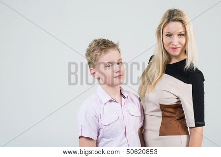 Mother with blond hair and a son with disheveled hair in the studio