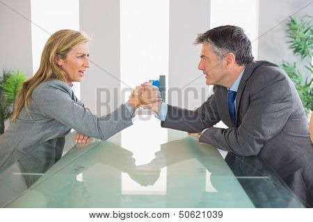 Two upset mature businesspeople having an arm wrestling sitting around a table at office