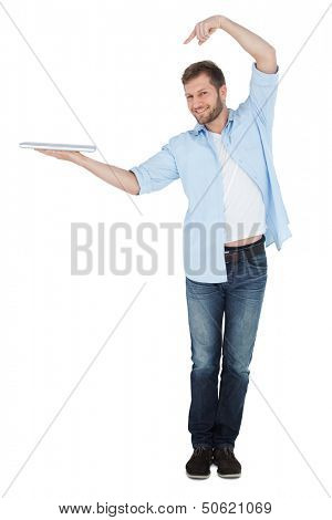 Happy model holding laptop on right hand with flair and looking at camera