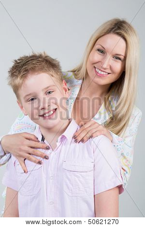 Happy smiling mother hugging young son with disheveled hair in the studio