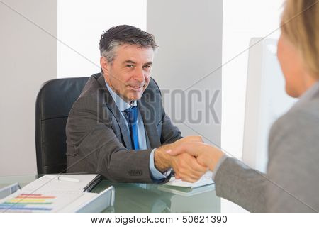 Cheerful mature businessman shaking the hand of a blonde interviewee in office