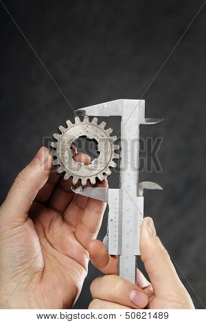 Man measuring the diameter of old cog with vernier caliper.